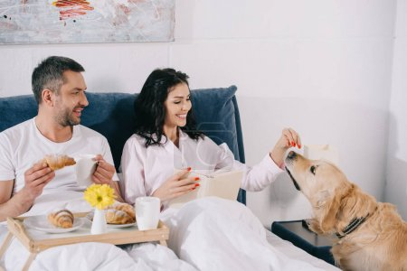 Photo for Cheerful woman touching cute dog near man holding cup and croissant in bed - Royalty Free Image