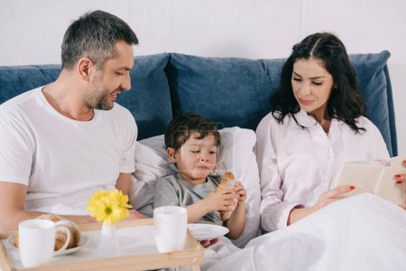 Photo for Happy parents looking at toddler son with croissant in bed - Royalty Free Image