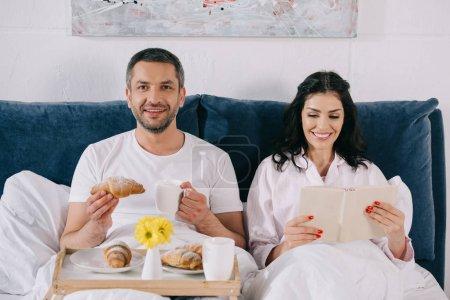 Photo pour Livre heureux de lecture de femme près du mari gai retenant le croissant et la tasse dans le lit - image libre de droit