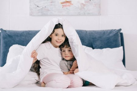 Photo for Cheerful kid sitting under blanket with cute toddler brother - Royalty Free Image