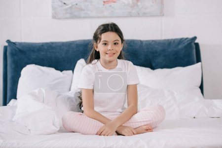 Photo for Happy kid smiling while sitting in bedroom and looking at camera - Royalty Free Image