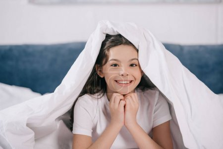 Photo for Happy kid smiling while sitting under blanket and looking at camera - Royalty Free Image