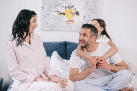 Photo pour Fille étreignant le père heureux près de la mère gaie dans la chambre à coucher - image libre de droit