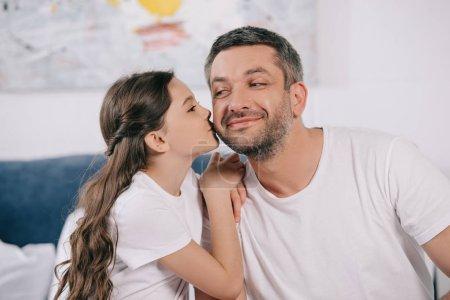 Photo pour Fille heureuse embrassant la joue du père gai dans la chambre à coucher - image libre de droit