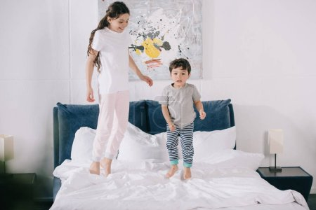 Photo for Happy child jumping on bed with adorable toddler brother - Royalty Free Image