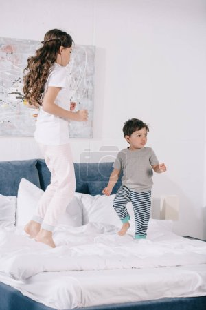 Foto de Cute child jumping on bed with adorable toddler brother - Imagen libre de derechos