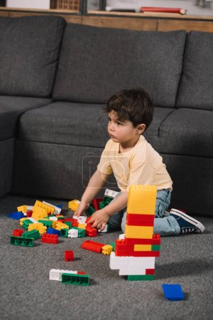 Foto de Selective focus of cute toddler playing with colorful toy blocks in living room - Imagen libre de derechos