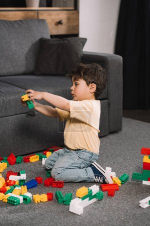 Photo for Cute toddler playing with colorful toy blocks in living room - Royalty Free Image