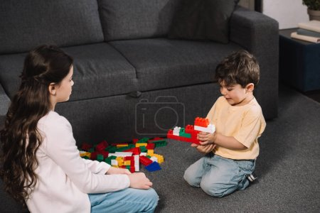 Photo for Cute kid looking at toddler brother playing with colorful toy blocks in living room - Royalty Free Image