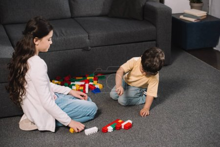 Foto de Cute child looking at toddler brother playing with colorful toy blocks in living room - Imagen libre de derechos
