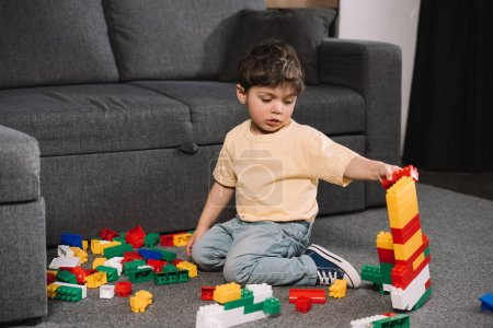 Photo for Adorable toddler playing with colorful toy blocks while sitting on floor in living room - Royalty Free Image