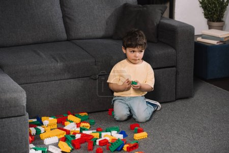 Photo for Cute toddler playing with colorful toy blocks while sitting on floor in living room - Royalty Free Image