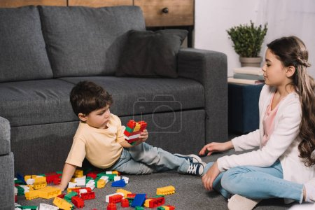 Photo for Adorable child looking at toddler brother playing with colorful toy blocks in living room - Royalty Free Image