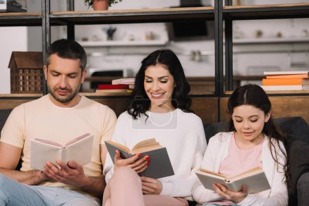 Photo for Happy family sitting on sofa and reading books in living room - Royalty Free Image