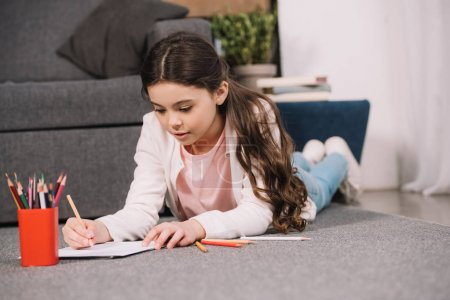 Photo for Selective focus of cute kid lying on floor and drawing on paper in living room - Royalty Free Image