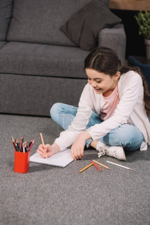 Photo for Cheerful kid sitting on floor and drawing on paper in living room - Royalty Free Image