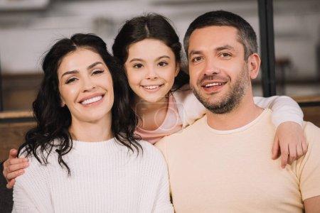 Photo pour Enfant heureux et parents souriants regardant l'appareil-photo à la maison - image libre de droit