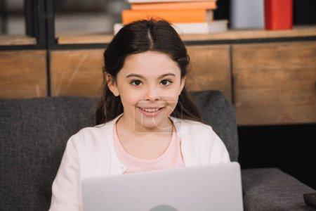 Foto de Happy kid looking at camera near laptop in living room - Imagen libre de derechos