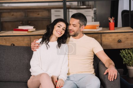 Photo for Happy man hugging cheerful wife while sitting on sofa at home - Royalty Free Image