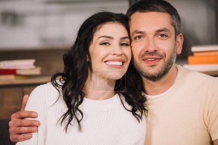 Foto de Happy man hugging attractive and cheerful woman at home - Imagen libre de derechos
