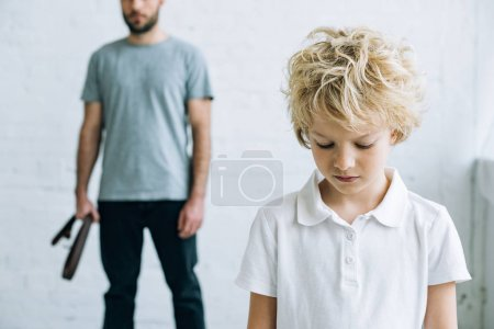 Photo for Cropped view of father with belt and upset son at home - Royalty Free Image