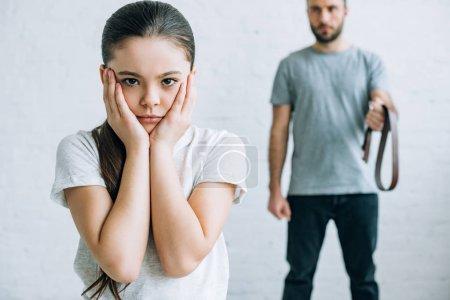 Photo pour Vue recadrée de père tenant ceinture et fille bouleversée à la maison - image libre de droit