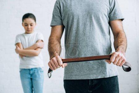 Photo pour Vue recadrée de la ceinture de fixation de père et fille bouleversée à la maison - image libre de droit