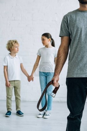 Photo for Partial view of abusive father with belt and kids holding hands - Royalty Free Image