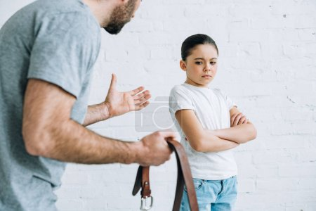 Photo for Partial view of father holding belt and scolding upset daughter at home - Royalty Free Image