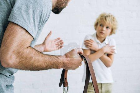 Photo pour Vue recadrée de la ceinture de fixation de père et fils de grondement à la maison - image libre de droit