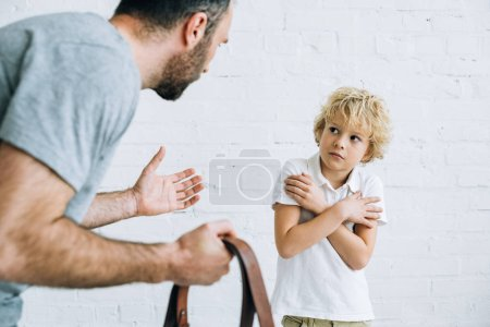Photo pour Cropped view of father holding belt and scolding son at home - image libre de droit