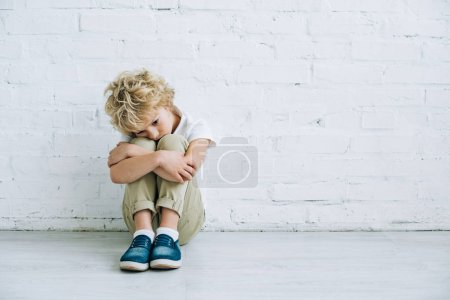 Foto de Upset preteen boy sitting on floor at home - Imagen libre de derechos