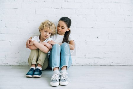 Photo for Upset sister and brother sitting on floor at home - Royalty Free Image