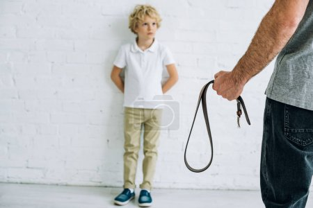 Photo for Cropped view of father holding belt and son having conflict - Royalty Free Image
