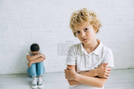 Photo pour Triste garçon debout avec les bras croisés tandis que sœur assise sur le sol et pleurant à la maison - image libre de droit