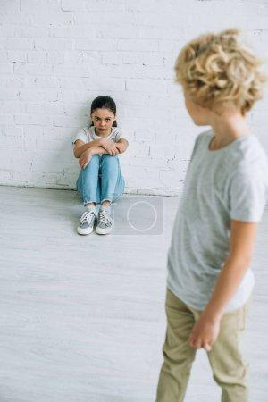 Photo pour Preteen garçon regardant soeur assis sur le sol - image libre de droit