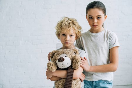 Foto de Sad sister and brother with teddy bear at home - Imagen libre de derechos