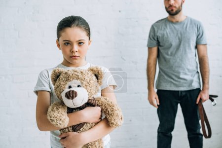 Photo for Partial view of abusive father with belt and sad daughter holding teddy bear - Royalty Free Image