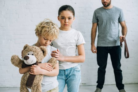 Photo for Partial view of abusive father with belt and sad kids with teddy bear - Royalty Free Image