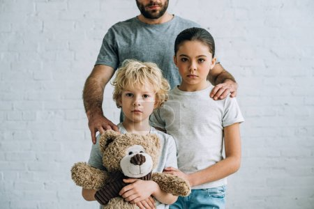 Photo for Partial view of father and kids with teddy bear at home - Royalty Free Image