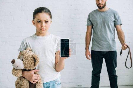 Photo pour Vue partielle du père et de la fille abusinves avec l'ours de nounours affichant le smartphone avec l'écran blanc - image libre de droit