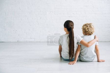 Photo for Back view of two kids embracing on floor at home - Royalty Free Image
