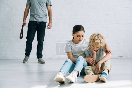 Photo for Partial view of abusive father and sad kids sitting on floor - Royalty Free Image