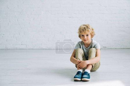 Photo pour Mignon petit garçon s'asseyant sur l'étage avec le sourire doucement et regardant l'appareil-photo - image libre de droit