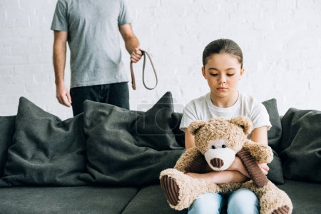 Photo for Partial view of abusive father with belt and sad daughter with teddy bear sitting on sofa - Royalty Free Image