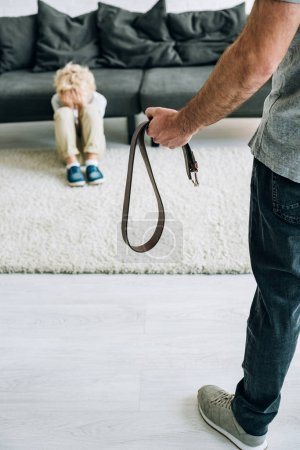 Photo for Partial view of abusive father holding belt and sad son sitting on carpet - Royalty Free Image