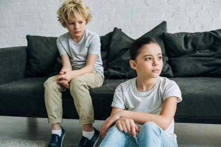 Photo pour Soeur et frère tristes sur le sofa dans le salon - image libre de droit