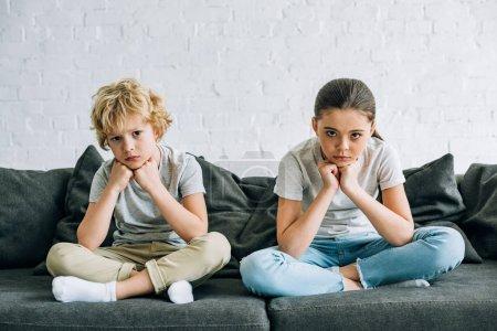 Photo pour Deux enfants tristes s'asseyant sur le sofa dans le salon - image libre de droit