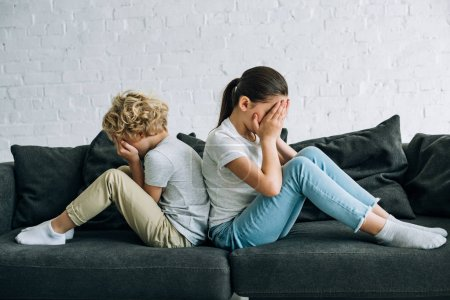 Photo for Two sad kids sitting on sofa in living room - Royalty Free Image