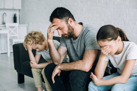 Photo for Two sad preteen children and father having conflict - Royalty Free Image